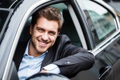 Mężczyzna w samochodzie z wypożyczalni aut korzystający z usługi car sharing